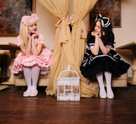 doll house: Young women dressed as dolls look at each other.