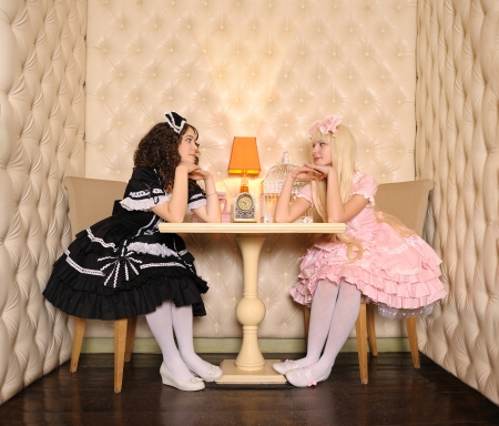 doll house: Young women dressed as dolls, sitting at a table in the doll house.
