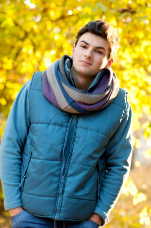 Young smiling man portrait in yellow autumn park. photo