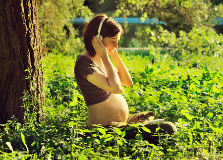 Young pregnant woman listening to a music at park. photo
