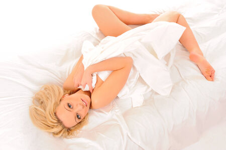 Bright picture of laying in bed sexy woman covering by sheets. photo