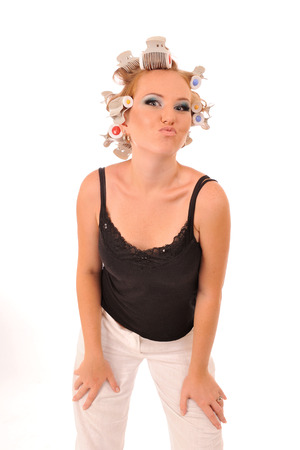 crazy girl: Funny young woman with curlers giving a kiss.