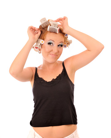 primp: Funny young woman makes hair curlers. Stock Photo