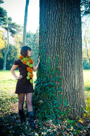 Young woman hiking in autumn park dressed in knitted dress and scarf. photo