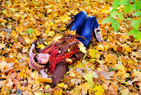 Happy woman portrait lying on autumn leaves in park and looking at camera.  photo