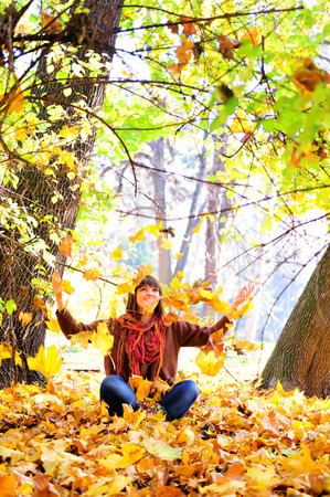 Happy young woman throwing autumn leaves in park. photo