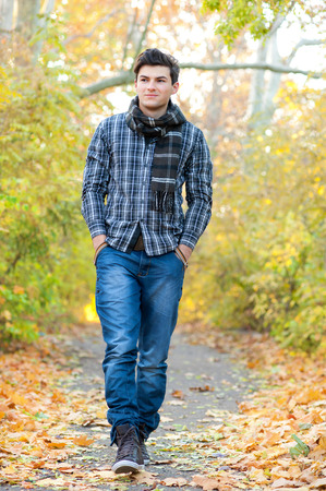 Jonge glimlachende man lopen in de herfst park. Stockfoto