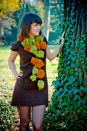Young woman posing outdoor dressed in handmade knitted dress and scarf. photo