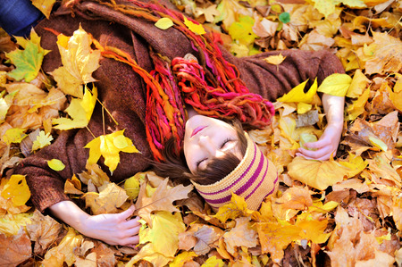 Girl lying in autumn leaves portrait, outdoor.  photo