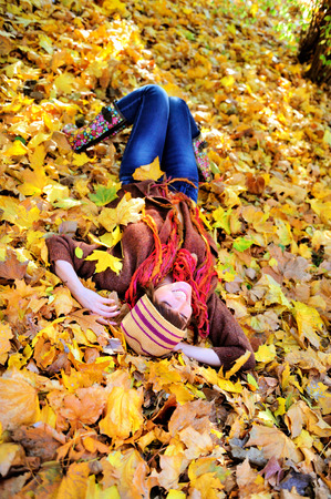 Smiling woman resting on autumn leaves in park.  photo