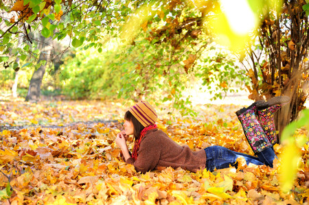Woman lying on her stomach on autumn leaves in park, side view. photo