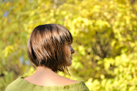 Beautiful young woman wearing short bob hairstyle autumn outdoor, focus on a hair.  photo