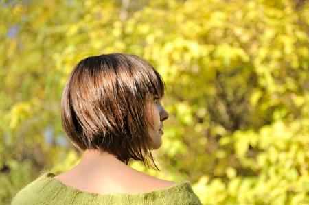 Mooie jonge vrouw, gekleed in korte bob kapsel herfst buiten, focus op een haar.