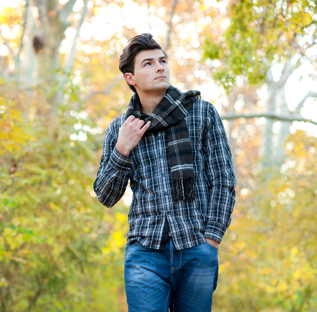checkered scarf: Handsome serious man dressed in a plaid scarf walking in autumn park. Stock Photo