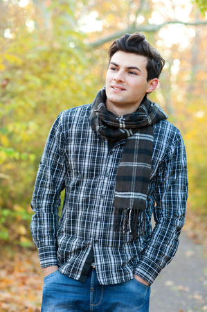 Portrait of the handsome smiling man dressed in a plaid shirt hiking in autumn park. photo