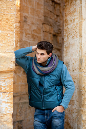 touched: Young stylish model man touched his hair, urban portrait.