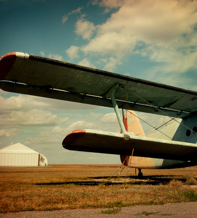 Plane wing against the hangar and autumn field. photo