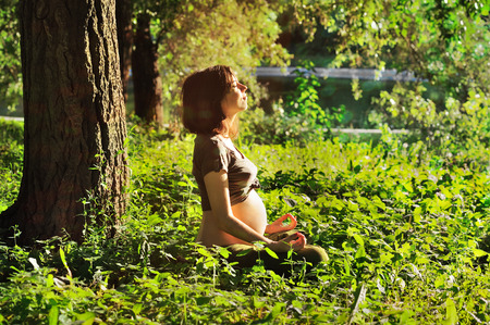 Young pregnant woman doing yoga in nature outdoors. photo