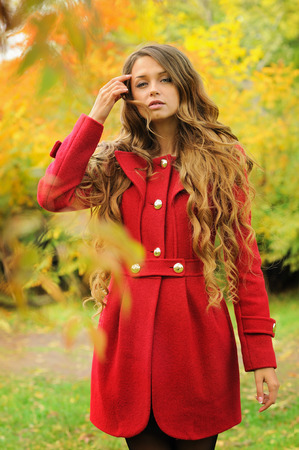 long red hair woman: Young fashion woman with long hair dressed in red coat posing in autumn park.
