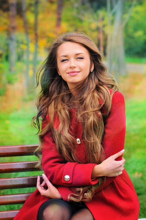 Portrait of a smiling woman dressed in red coat sitting in autumn park. photo