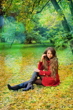 Young woman in red coat sitting in autumn park. photo