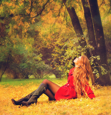 Young woman dressed in red coat relaxing in autumn park. photo