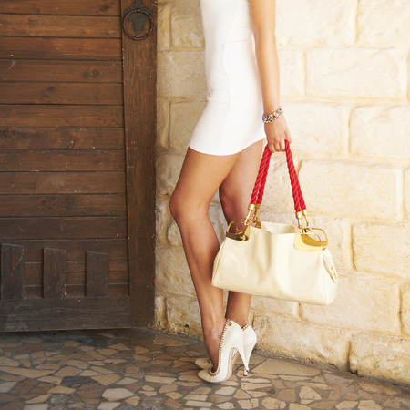 Sexy female shod white high heel shoes holding in a hand fashion bag. photo