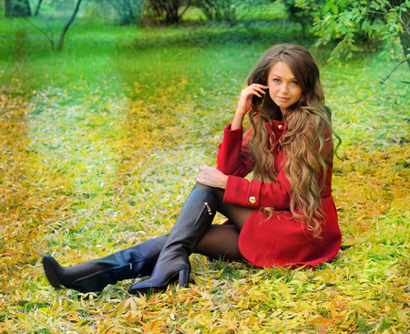 Pretty woman with long hair rest in autumn park. photo