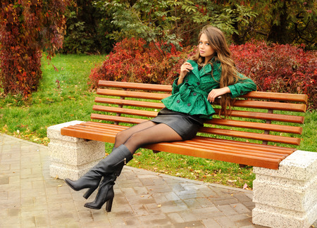 short skirt: Cute girl sitting on a bench in the park. Stock Photo