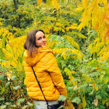 hoody: Молодая симпатичная женщина в желтом капюшоном, ходить в осеннем лесу.