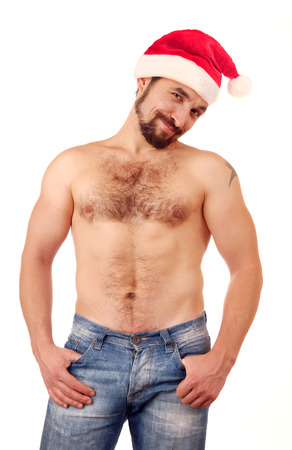 Handsome man with naked torso in Santa hat. Stock Photo