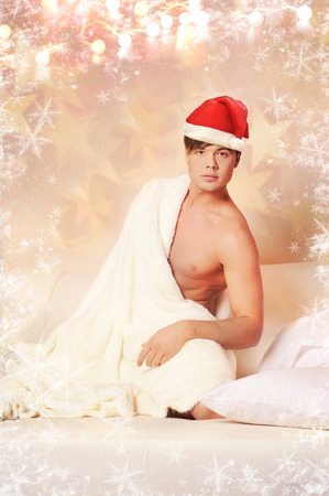 Sexy model man in santa hat sitting on bed.