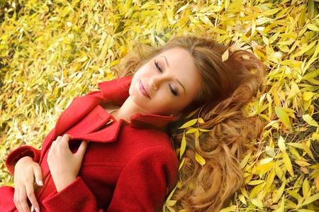 Portrait of a cute smiling woman in red coat lying in autumn leaves in park. photo