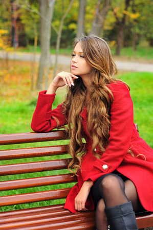 Young woman dressed in red coat sitting in autumn park on a bench. photo