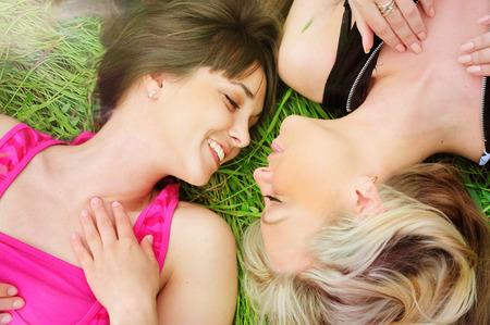 lesbians: Retrato al aire libre de una pareja de lesbianas amigas que pone en hierba, sonriendo y mirando el uno al otro.