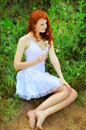 Cute redhead woman in white dress sitting on a grass in park with dandelions in her hands. photo