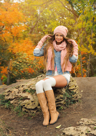 knit: Smiling young woman wearing a knit cap and scarf posing in the autumn park.