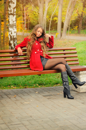 Smiling woman dressed in red coat sitting in autumn park on a bench.