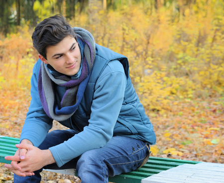 thanksgiving adult: Young smiling man portrait sitting in autumn park on a bench.