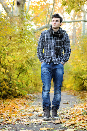 handsome young man: Young handsome man walking in autumn park.