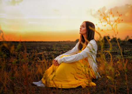 woman in field: Bright woman relax sitting on a sunset autumn field.