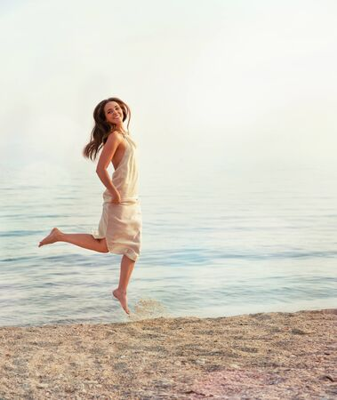 young adult woman: Happy woman jumping against sea backdrop.