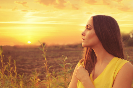 Beautiful young woman profile portrait against sunset autumn field, gazing into infinity.