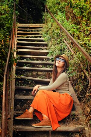 falda: Muchacha ocasional que desgasta la falda larga de color naranja sentado en el viejo aire libre escaleras de madera.