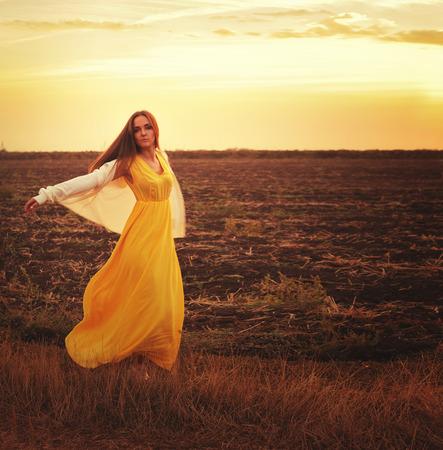 donna che balla: Moda donna vestita in abito lungo giallo e jersey bianco ballare su un campo di tramonto autunnale.