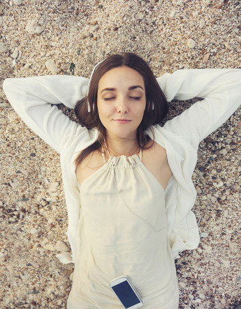 view woman: Young smiling woman outdoor portrait lying on a sea sand and listening music, top view.