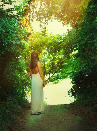 way: Back view of a slim fashion woman dressed in long white dress illuminated by sunlight standing on a forest way.