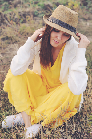 yellow fleece: Young woman dressed in yellow dress, white jersey and hat sitting on a deadwood autumn field.