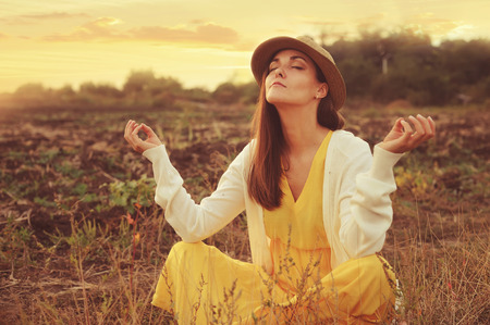 Young attractive female meditate sitting on a deadwood autumn field.