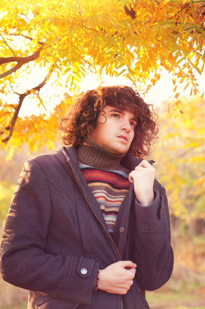 oudoor: Young adult fashion man portrait dressed in gray jacket and striped sweater, oudoor in autumn park.